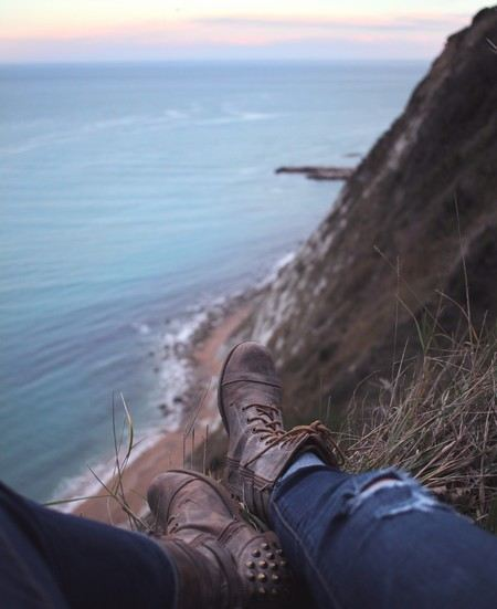 só se vêm os jeans e botas de alguém sentado a pique sobre uma falésia que dá sobre o mar